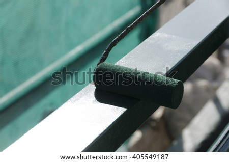 worker while painting a railing with a roller