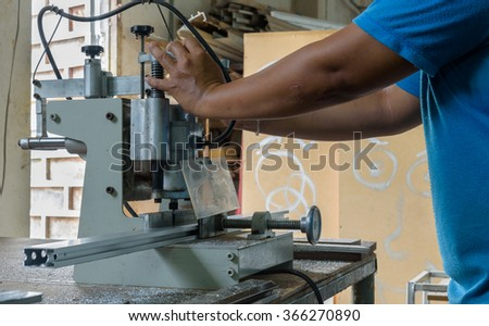 worker who use machine for drilling aluminium