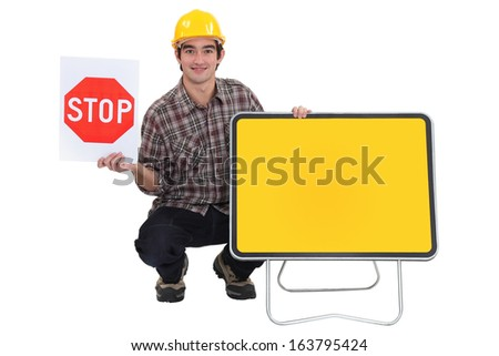 Worker with a blank road sign - stock photo
