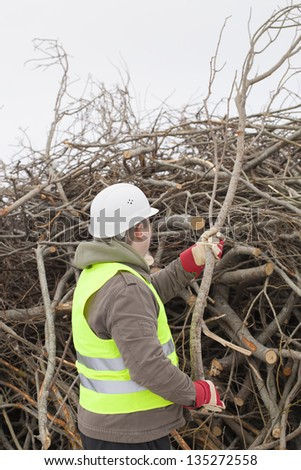 Worker with a branch in hands at the big pile of twigs - stock photo