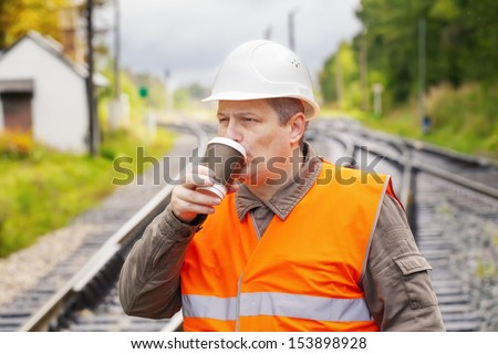 Worker with a coffee on the railway in summer - stock photo