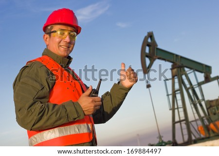Worker with a portable radio at an oil pump, focus on the man, background soft focus