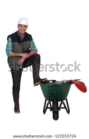 Worker with a wheelbarrow - stock photo