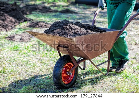Worker with a wheelbarrow full of compost - stock photo