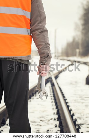 Worker with adjustable wrench in the hands  on railway crossings - stock photo