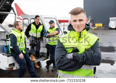 Worker With Arms Crossed Standing While Colleagues Communicating