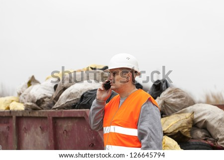 Worker with cell phone near garbage and container - stock photo