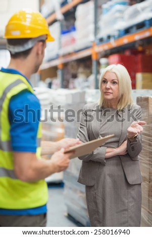 Worker with clipboard speaking with his manager in warehouse - stock photo