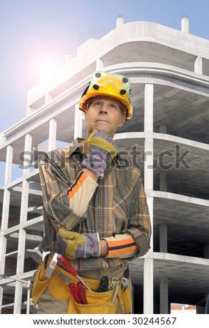 Worker with construction site in the background - stock photo