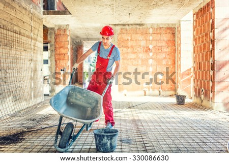 worker with empty wheelbarrow on construction site - stock photo