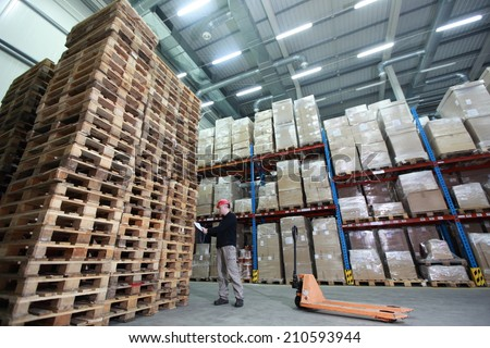 worker with hand pallet truck preparing delivery - stack of wooden pallets in storehouse - stock photo