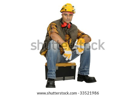Worker with hat seated in a  tool box isolated in white