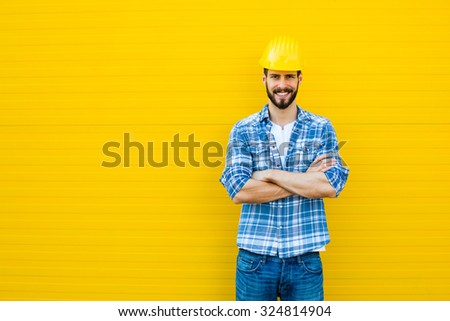 worker with helmet and yellow plaid shirt near a wall - stock photo