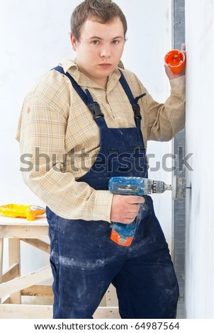 worker with mobile drill wall for installing power socket - stock photo