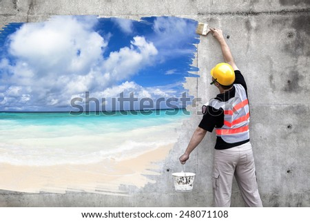 worker with paint brushes drawing summer beach on the wall - stock photo