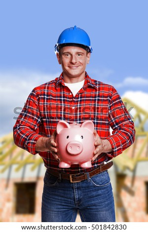 Worker with piggy bank. Construction and house renovation concept.