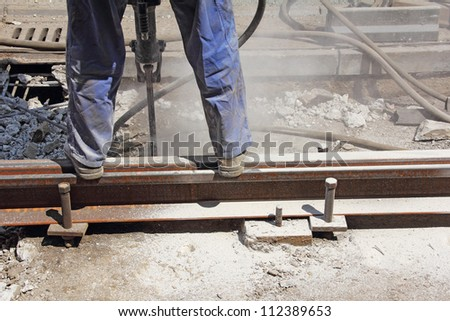 Worker with pneumatic hammer drill equipment breaking asphalt at construction site