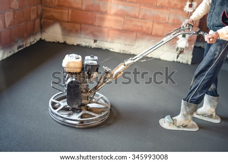 Worker with power trowel tool finishing concrete floor, smooth concrete surface. - stock photo