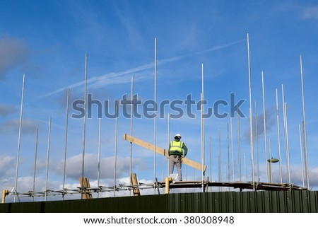 Worker with protective clothes holding wooden board on a construction site - stock photo
