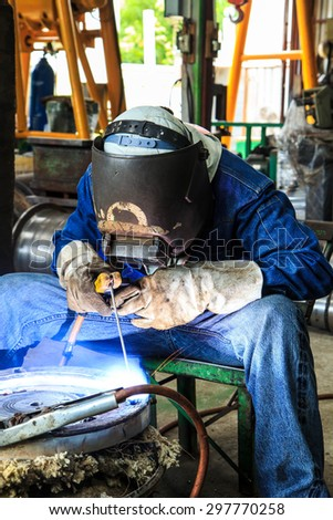 Worker with protective mask sparks piping welding - stock photo