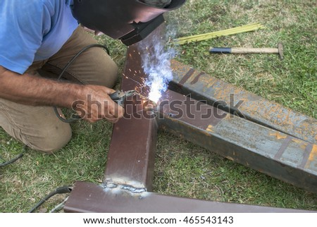 Worker with protective mask welding metal, outdoor
