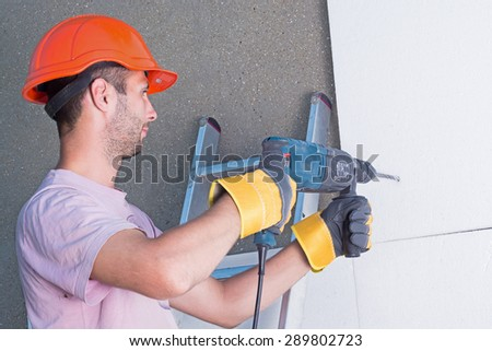 Worker with rock-drill warms the wall