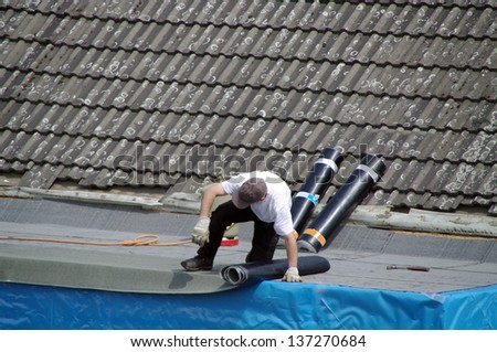 Worker with roll of bitumen on roof - stock photo