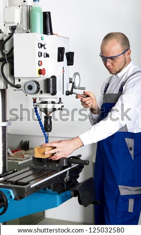 worker with safety glasses at milling machine - stock photo