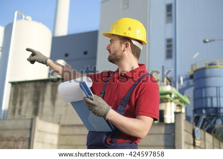 worker with safety helmet outside a factory - stock photo