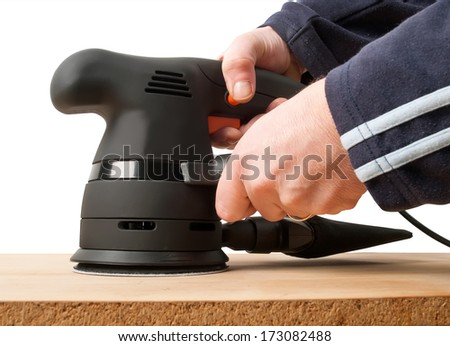 worker with sander machine working on wooden surface - stock photo