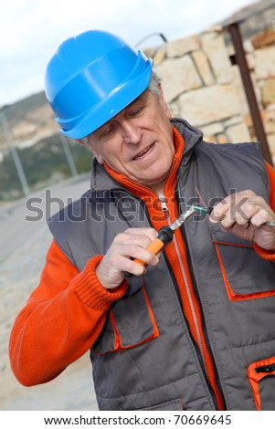 Worker with security helmet installing gate system