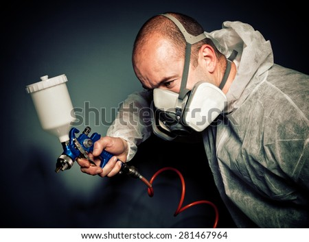 worker with spray-gun and protection clothes - stock photo