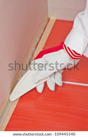 worker with tool smooth silicone sealant on corner with tiles - stock photo