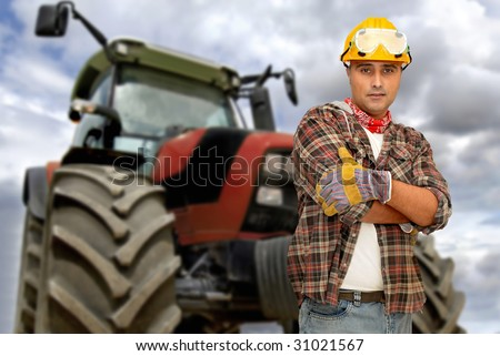 Worker with tractor on the background - stock photo