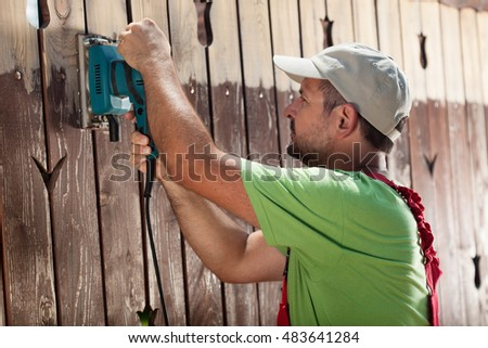 Worker with vibrating sander removing old paint from wooden fence