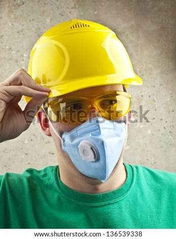 worker with yellow helmet and mask over concrete wall - stock photo