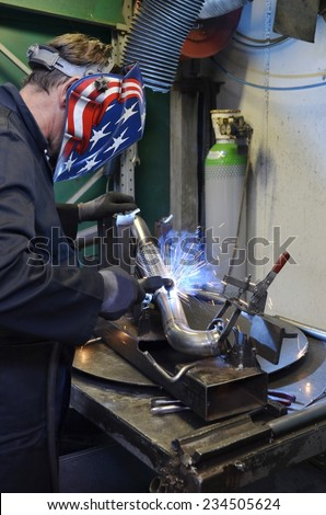 Worker work hard with welding process in production plant into a metal warehouse. Construction of mufflers for cars
