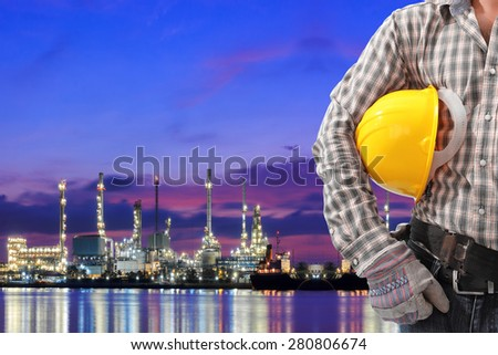 Worker working at oil refinery petrochemical industrial plant at twilight - stock photo