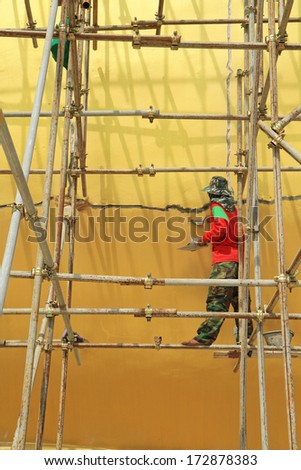 Worker working during renovation of big buddha statue at Wat Muang, Thailand.