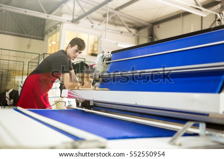 Worker working on fabric spreading machine in fabric industry