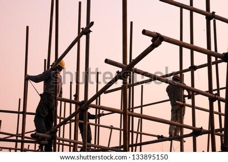 worker working on scaffold near sunset - stock photo