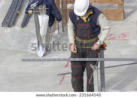 Worker working with armature on construction site - stock photo
