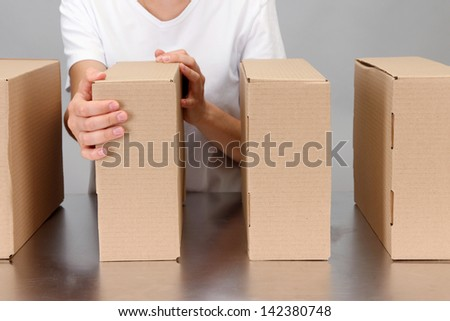 Worker working with boxes at conveyor belt, on grey background - stock photo