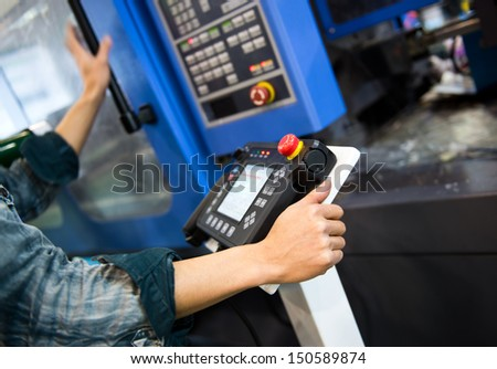worker working with cnc machine at workshop. - stock photo