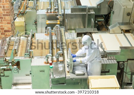 Worker working with machine in bakery factory - stock photo