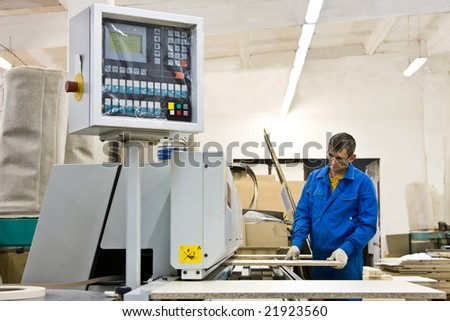 Worker working with wood paneling machine