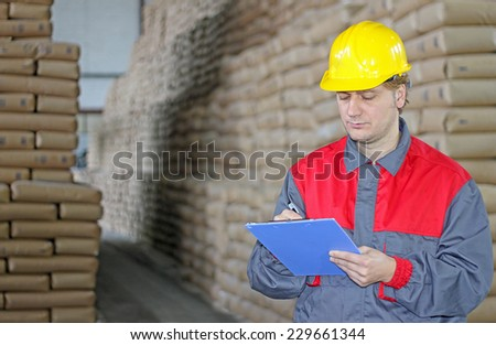 Worker writing on clipboard in warehouse, sugar bags - stock photo