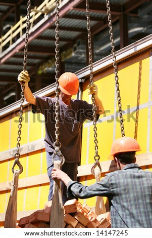 Workers and bricks on construction site - stock photo