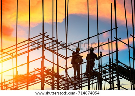 workers and construction site at sunset
