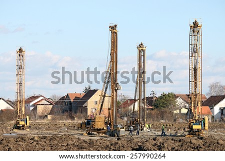 workers and four hydraulic drilling machines on construction site  - stock photo